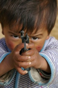 A child playing with a broken gun.